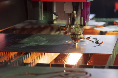 The CNC fiber laser cutting machine cutting the sheet metal plate with the sparking light.